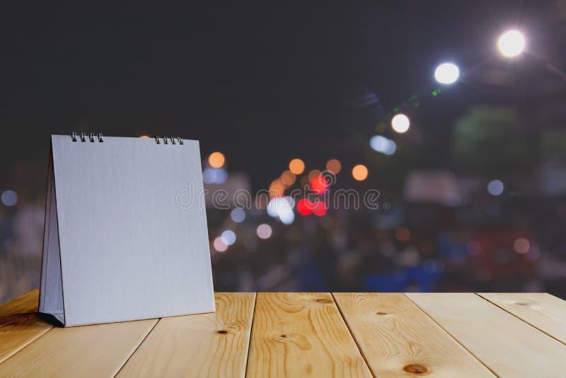 Άσπρο ημερολόγιο στον ξύλινο πίνακα στο σκοτεινό φως bokeh στοκ εικόνα
