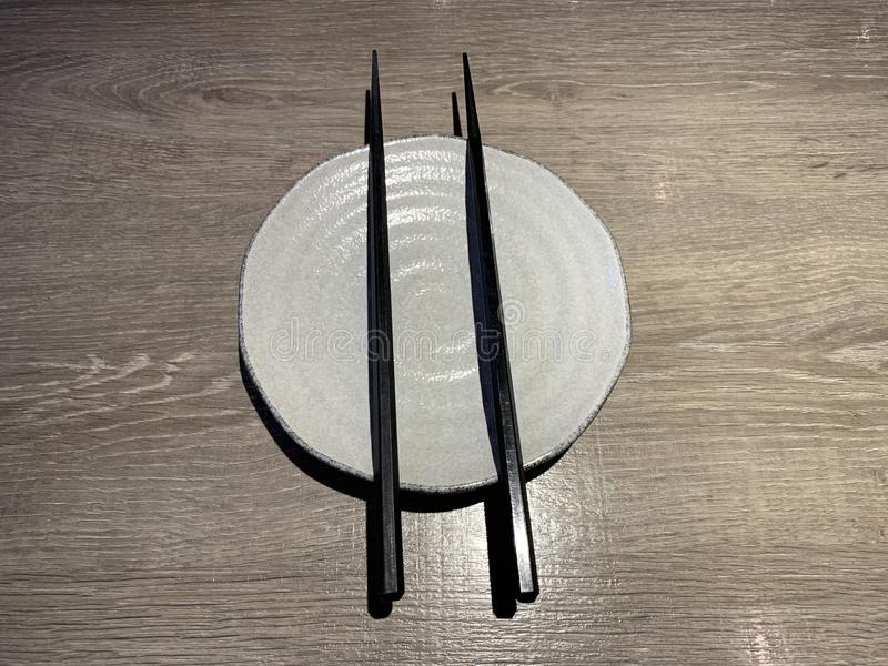 Άσπρο ιαπωνικό πιάτο με chopstick στον ξύλινο πίνακα στοκ εικόνες
