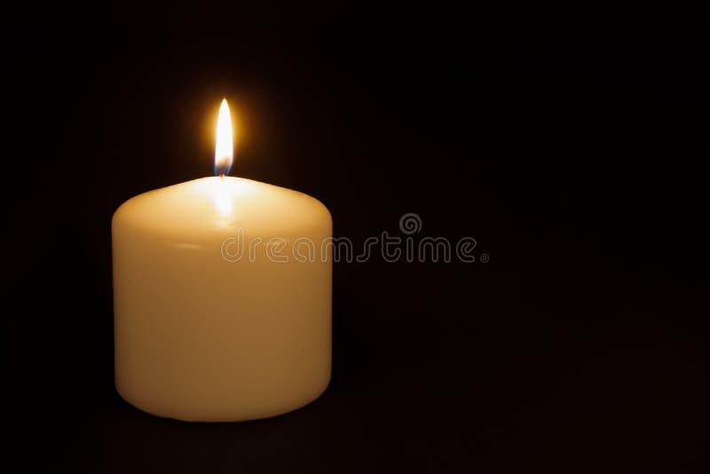 Άσπρο κάψιμο κεριών σε ένα μαύρο κλίμα στοκ εικόνες με δικαίωμα ελεύθερης χρήσης