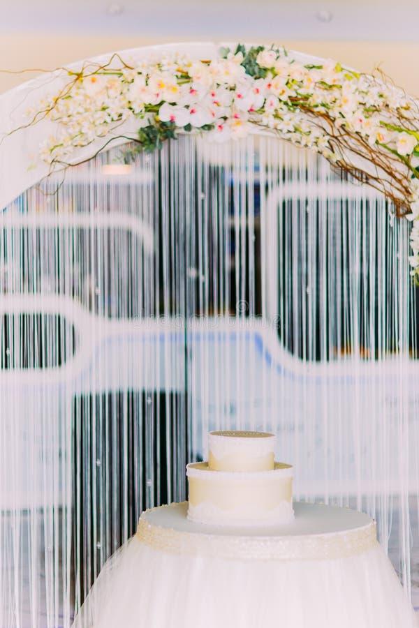 Άσπρο κέικ στο διακοσμημένο πίνακα Αψίδα με τη floral διακόσμηση ως υπόβαθρο στοκ εικόνα με δικαίωμα ελεύθερης χρήσης