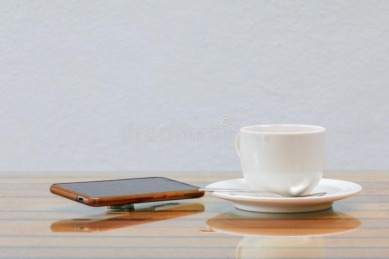 Άσπρο και κινητό τηλέφωνο φλυτζανιών καφέ στον πίνακα γυαλιού ξύλινο και ένα υπόβαθρο τοίχων τσιμέντου στοκ εικόνες με δικαίωμα ελεύθερης χρήσης