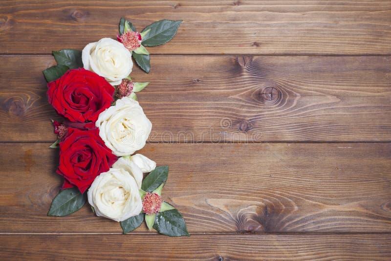 Άσπρο και κόκκινο ντεκόρ τριαντάφυλλων στο ξύλινο υπόβαθρο στοκ φωτογραφία