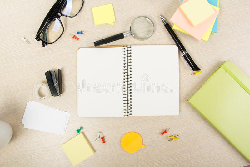 Άσπρο κενό ανοικτό βιβλίο σημειώσεων Επιτραπέζιο γραφείο γραφείων με το σύνολο ζωηρόχρωμων προμηθειών, φλυτζάνι, μάνδρα, μολύβια, στοκ εικόνα με δικαίωμα ελεύθερης χρήσης