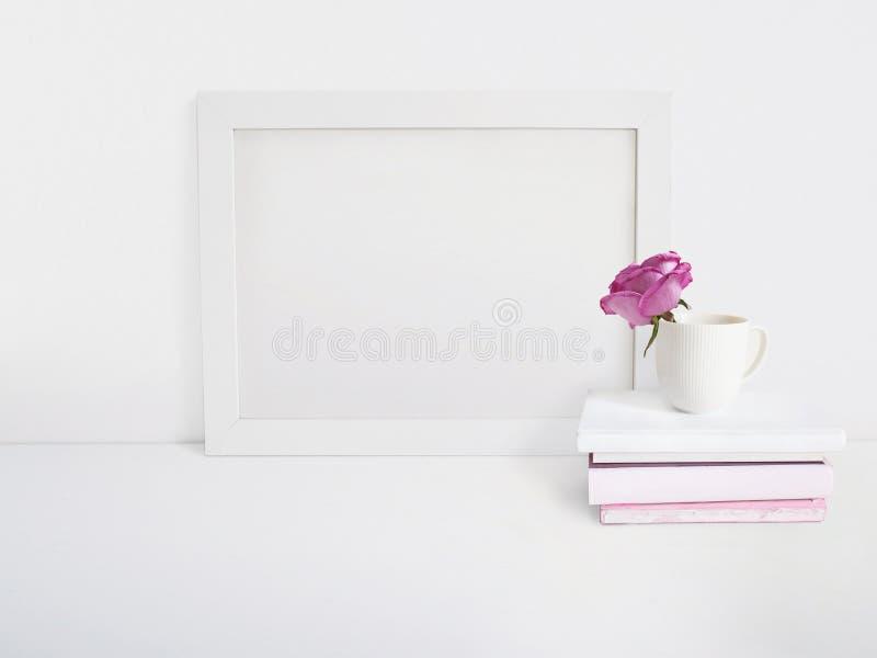 Άσπρο κενό ξύλινο πρότυπο πλαισίων με ένα ροδαλό λουλούδι σε ένα φλυτζάνι πορσελάνης και έναν σωρό των βιβλίων που βρίσκονται στο στοκ εικόνες