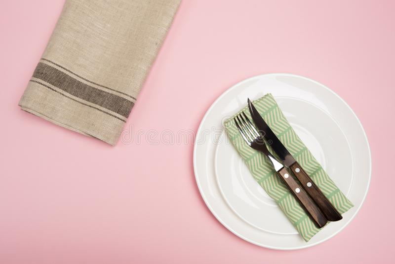 Άσπρο κενό πιάτο με την υφαντική πετσέτα μαχαιριών και δικράνων στο ρόδινο υπόβαθρο στοκ φωτογραφία με δικαίωμα ελεύθερης χρήσης