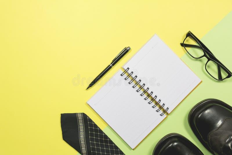 Άσπρο κενό σημειωματάριο με τις προμήθειες γραφείων στο κίτρινο υπόβαθρο W στοκ φωτογραφία με δικαίωμα ελεύθερης χρήσης