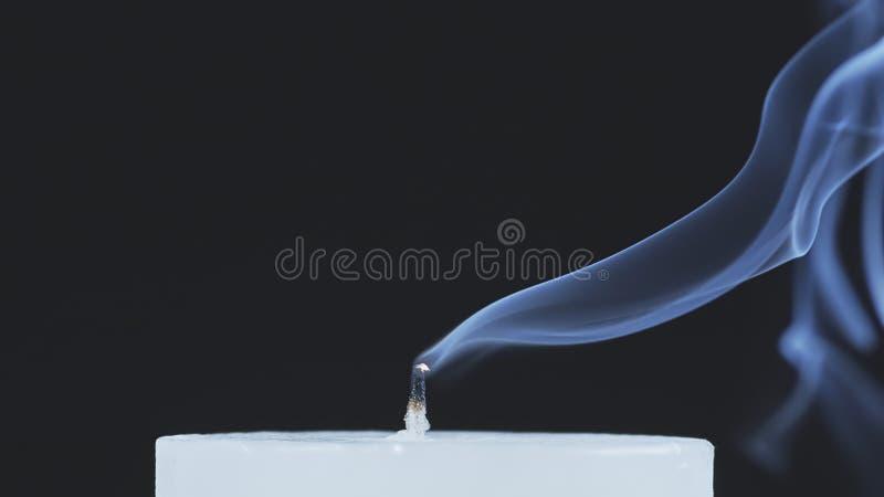 Άσπρο κερί που καπνίζει σε ένα μαύρο υπόβαθρο στοκ εικόνες
