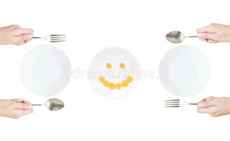 Άσπρο κεραμικό πιάτο κινηματογραφήσεων σε πρώτο πλάνο με το ανοξείδωτο δίκρανο και κουτάλι στο χέρι γυναικών με το πρόσωπο χαμόγε στοκ φωτογραφίες με δικαίωμα ελεύθερης χρήσης