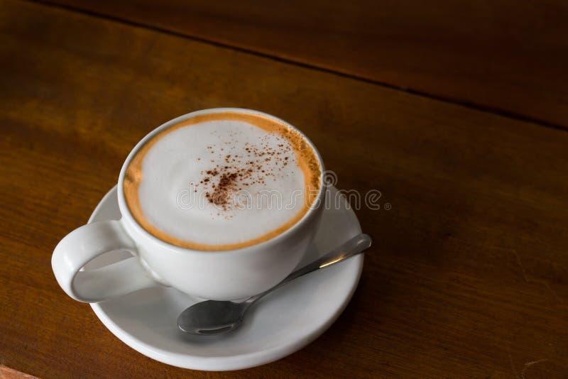 Άσπρο κεραμικό φλυτζάνι καφέ στον ξύλινο πίνακα στοκ φωτογραφία