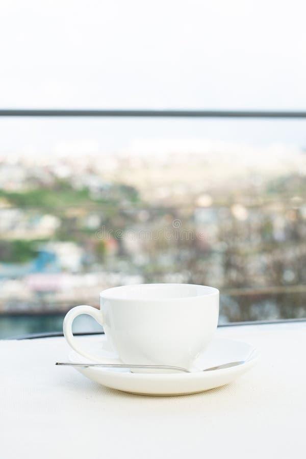 Άσπρο κεραμικό φλυτζάνι με το πιατάκι στον πίνακα υπαίθριο στοκ φωτογραφία με δικαίωμα ελεύθερης χρήσης