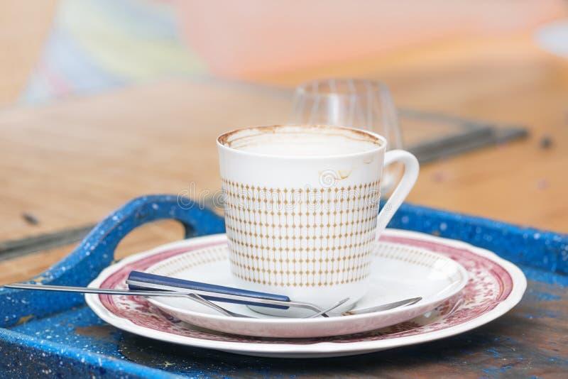 Άσπρο κεραμικό φλυτζάνι με τα ίχνη καφέ πέρα από τον μπλε δίσκο στοκ φωτογραφίες
