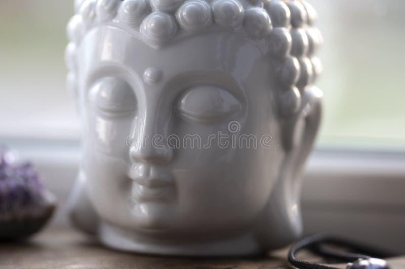 Άσπρο κεφάλι του Βούδα στο υπόβαθρο windowsill Εγχώριος βωμός, πνευματική τελετουργική θέση περισυλλογής Το σύμβολο θρησκείας, κλ στοκ εικόνες