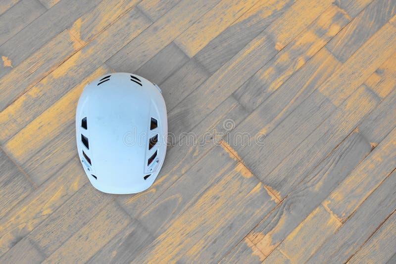 Άσπρο κράνος αναρρίχησης που χρησιμοποιείται επίσης στις αλπικές ή βιομηχανικές κατασκευές στο ξύλινο υπόβαθρο με τις διαγώνιες σ στοκ φωτογραφία