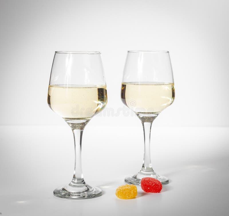 άσπρο κρασί γυαλιού Πολύχρωμες καραμέλες σε ένα άσπρο υπόβαθρο στοκ φωτογραφία με δικαίωμα ελεύθερης χρήσης