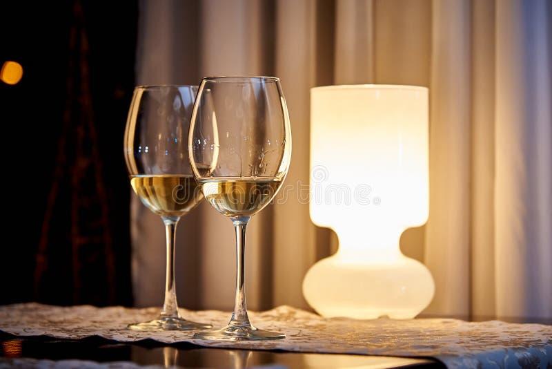 Άσπρο κρασί γυαλιού στον πίνακα με έναν καίγοντας λαμπτήρα σε ένα άνετο εστιατόριο στοκ φωτογραφία με δικαίωμα ελεύθερης χρήσης