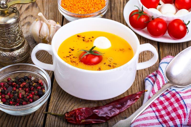 Άσπρο κύπελλο με τη σούπα κρέμας των φακών, των ντοματών και της μοτσαρέλας στοκ φωτογραφία