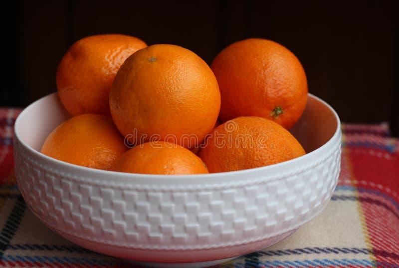 Άσπρο κύπελλο της Κίνας που γεμίζουν με τα succulent juicy φρέσκα πορτοκάλια ένα ελεγμένο κόκκινο κάλυμμα Μαύρη ανασκόπηση στοκ φωτογραφίες με δικαίωμα ελεύθερης χρήσης