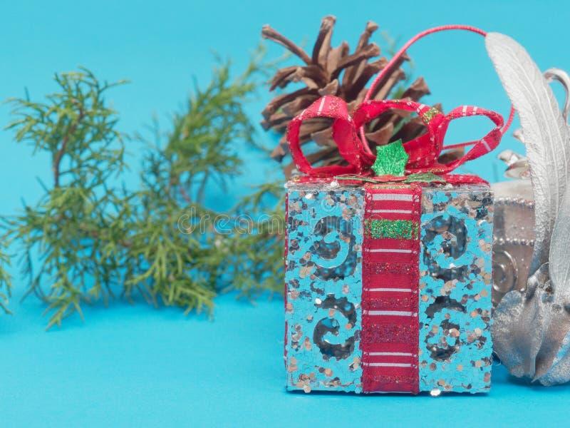 Άσπρο λαμπρό ασημένιο κιβώτιο δώρων με την κόκκινα κορδέλλα και το τόξο με το άσπρους τετραγωνικούς και στρογγυλούς κιβώτιο δώρων στοκ φωτογραφίες
