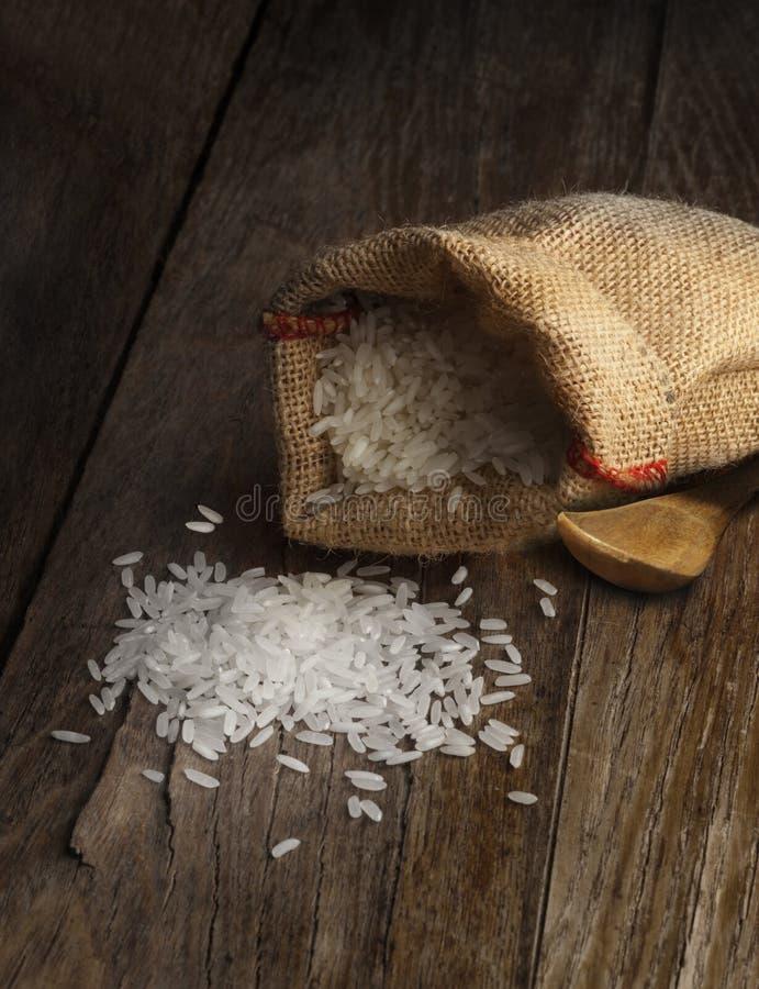 Άσπρο μακρύ ρύζι burlap στο σάκο στον ξύλινο πίνακα στοκ εικόνες