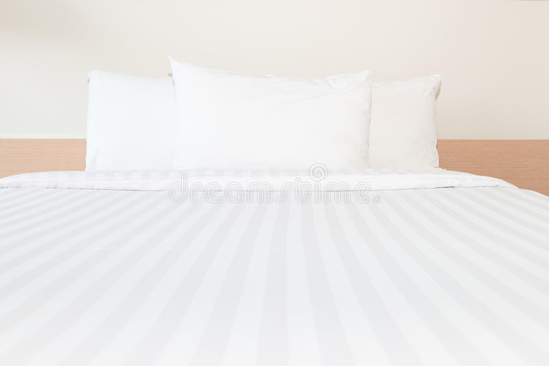Άσπρο μαξιλάρι και άσπρο κρεβάτι στο δωμάτιο κρεβατιών στοκ εικόνα