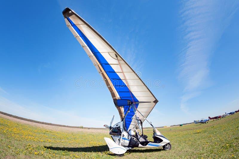 Άσπρο μηχανή-ανεμοπλάνο στο καθάρισμα που περιμένει τη στροφή τους για να πετάξει στοκ εικόνα