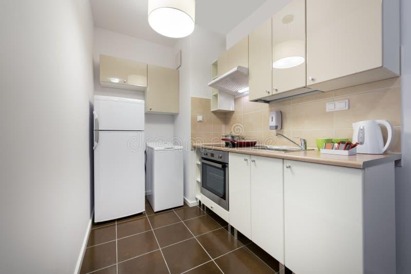 Άσπρο, μικρό και συμπαγές εσωτερικό σχέδιο κουζινών στοκ φωτογραφίες
