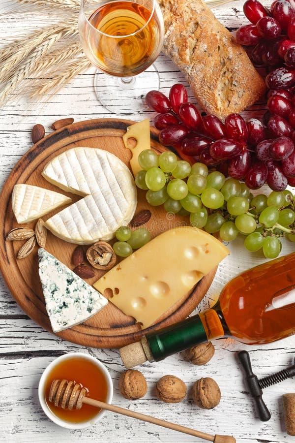 Άσπρο μπουκάλι, σταφύλι, μέλι, τυρί και wineglass κρασιού στο λευκό ξύλινο πίνακα στοκ εικόνες με δικαίωμα ελεύθερης χρήσης