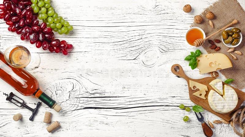 Άσπρο μπουκάλι, σταφύλι, μέλι, τυρί και wineglass κρασιού στο λευκό ξύλινο πίνακα στοκ φωτογραφίες