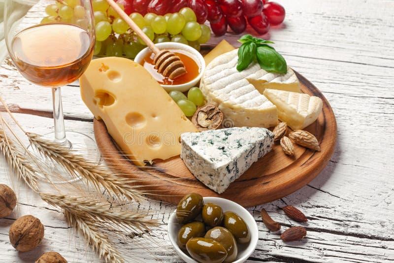 Άσπρο μπουκάλι, σταφύλι, μέλι, τυρί και wineglass κρασιού στο λευκό ξύλινο πίνακα στοκ φωτογραφία