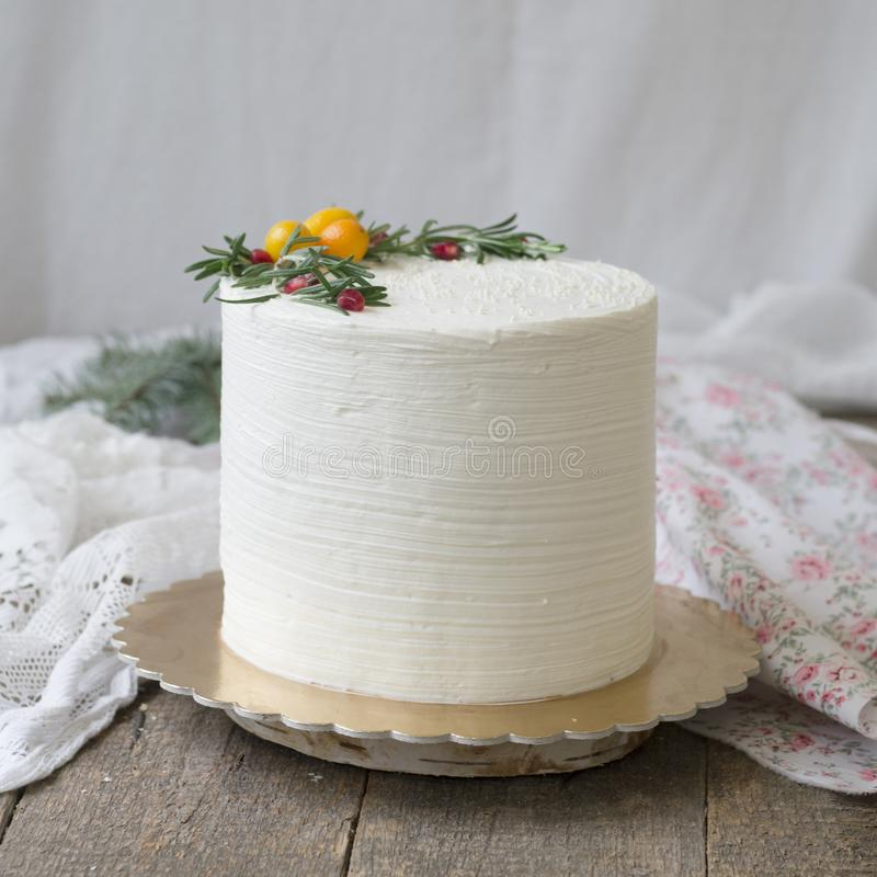 Άσπρο νέο κέικ έτους ή Χριστουγέννων, που διακοσμούνται με το κουμκουάτ, κλαδάκια του δεντρολιβάνου και τα βακκίνια σε έναν ξύλιν στοκ φωτογραφία με δικαίωμα ελεύθερης χρήσης