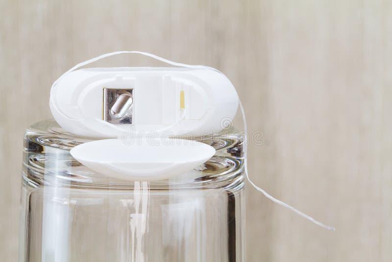 Άσπρο οδοντικό νήμα στο γυαλί στο θολωμένο ξύλινο υπόβαθρο στο λουτρό στοκ εικόνα με δικαίωμα ελεύθερης χρήσης