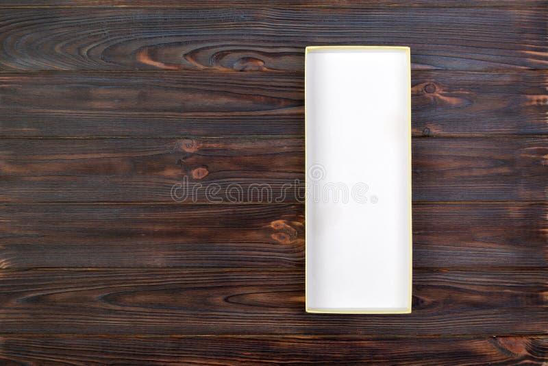 Άσπρο ορθογώνιο κενό ανοικτό κιβώτιο, τοπ άποψη στο σκοτεινό ξύλινο υπόβαθρο Τοπ όψη στοκ φωτογραφία με δικαίωμα ελεύθερης χρήσης