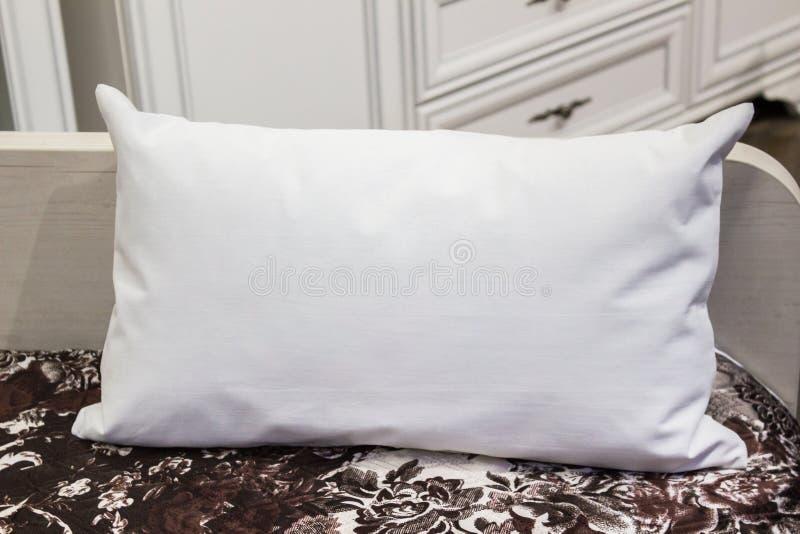Άσπρο οσφυικό μαξιλάρι σε ένα κρεβάτι, πρότυπο περίπτωσης εσωτερική φωτογραφία στοκ εικόνα