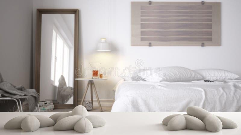 Άσπρο πίνακας, γραφείο ή ράφι με πέντε μαλακά άσπρα μαξιλάρια με μορφή των αστεριών ή τα λουλούδια, πέρα από τη θολωμένη Σκανδινα στοκ εικόνα με δικαίωμα ελεύθερης χρήσης