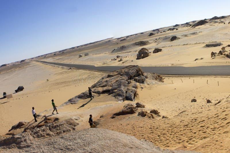 Άσπρο πανόραμα βουνών ερήμων με έναν δρόμο που τρέχει στον ορίζοντα στοκ εικόνα