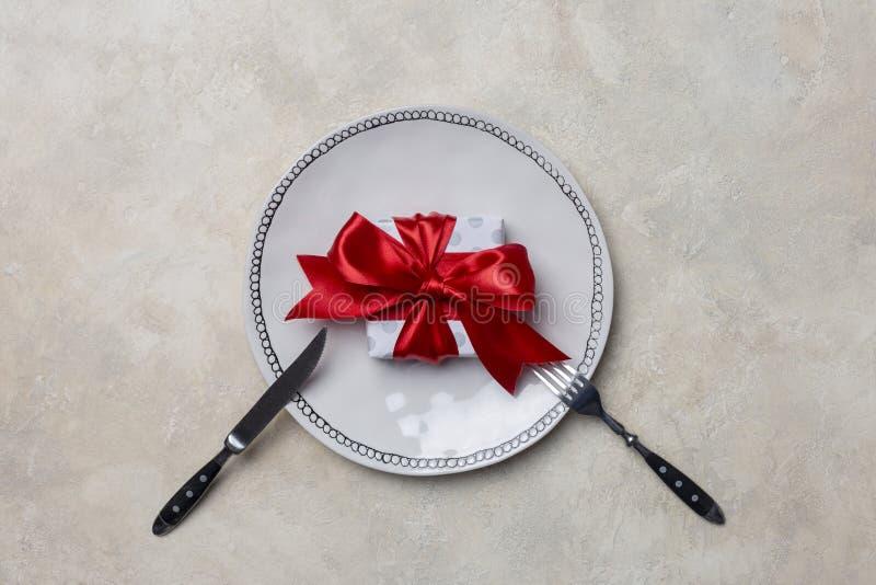 Άσπρο πιάτο με το κιβώτιο δώρων, με το δίκρανο και το μαχαίρι στο άσπρο υπόβαθρο για την ημέρα του βαλεντίνου στοκ φωτογραφία με δικαίωμα ελεύθερης χρήσης