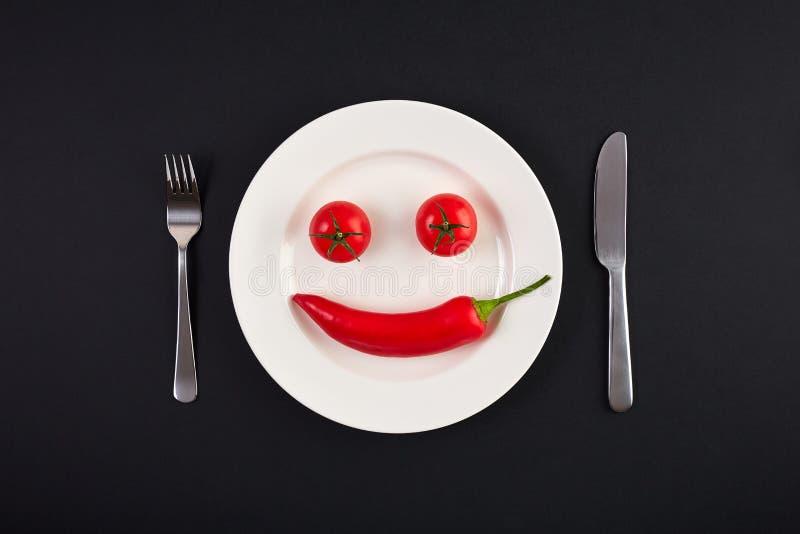 Άσπρο πιάτο με το πιπέρι τσίλι και ντομάτα ως χαμόγελο fac στοκ φωτογραφίες