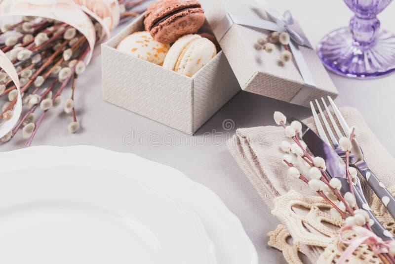 Άσπρο πιάτο, πορφυρό γυαλί, μαχαιροπήρουνα, παρόν κιβώτιο με macaroons και τους κλαδίσκους ιτιών γατών στοκ φωτογραφία με δικαίωμα ελεύθερης χρήσης