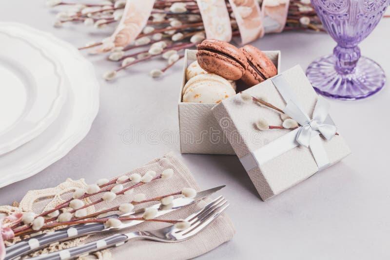 Άσπρο πιάτο, πορφυρό γυαλί, μαχαιροπήρουνα, παρόν κιβώτιο με macaroons και τους κλαδίσκους ιτιών γατών στοκ εικόνα