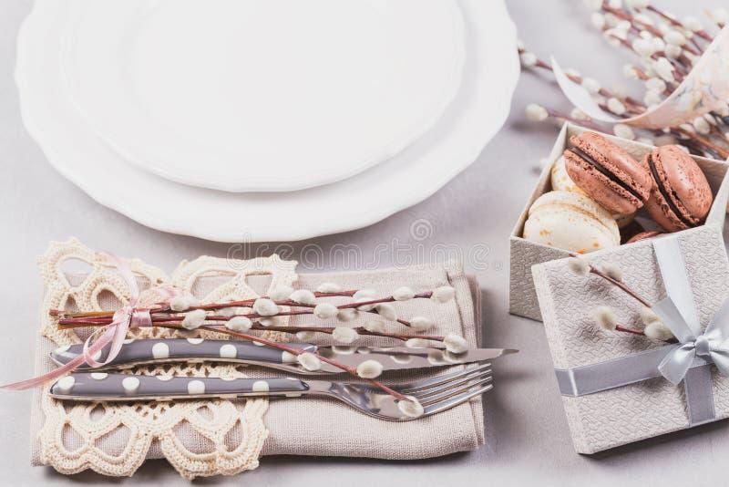 Άσπρο πιάτο, πορφυρό γυαλί, μαχαιροπήρουνα, παρόν κιβώτιο με macaroons και τους κλαδίσκους ιτιών γατών στοκ εικόνα με δικαίωμα ελεύθερης χρήσης