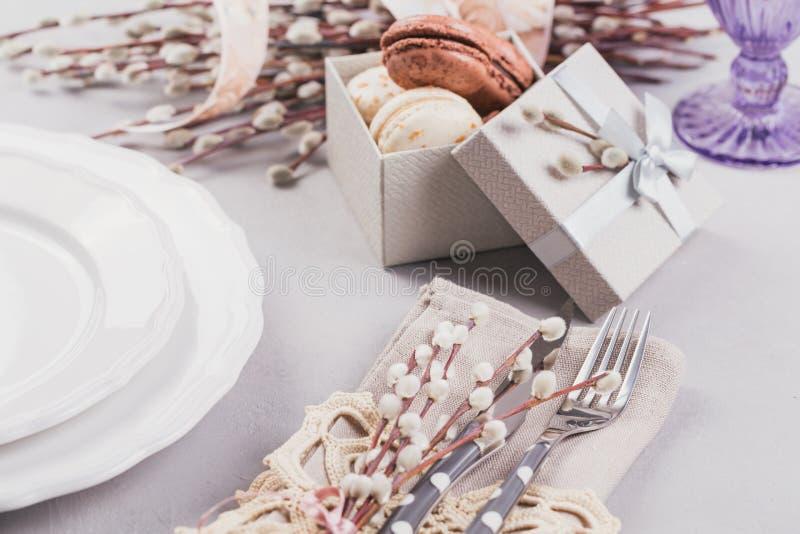 Άσπρο πιάτο, πορφυρό γυαλί, μαχαιροπήρουνα, παρόν κιβώτιο με macaroons και τους κλαδίσκους ιτιών γατών στοκ φωτογραφία