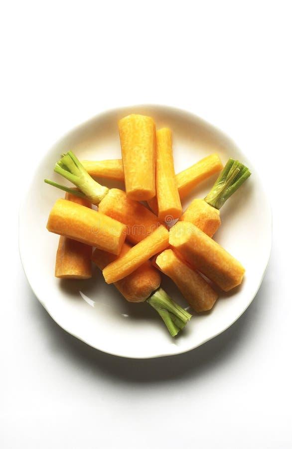Άσπρο πιάτο των ξεφλουδισμένων πορτοκαλιών πράσινων φύλλων καρότων στοκ εικόνες