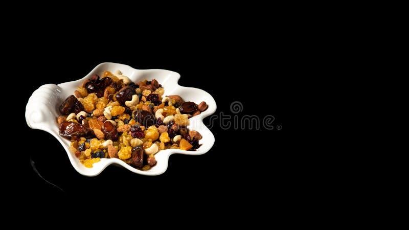 Άσπρο πιάτο των ξηρών καρπών στο μαύρο υπόβαθρο, με την αντανάκλαση Μίγμα των καρυδιών και των μούρων: σταφίδες, φουντούκι, τα δυ στοκ εικόνα