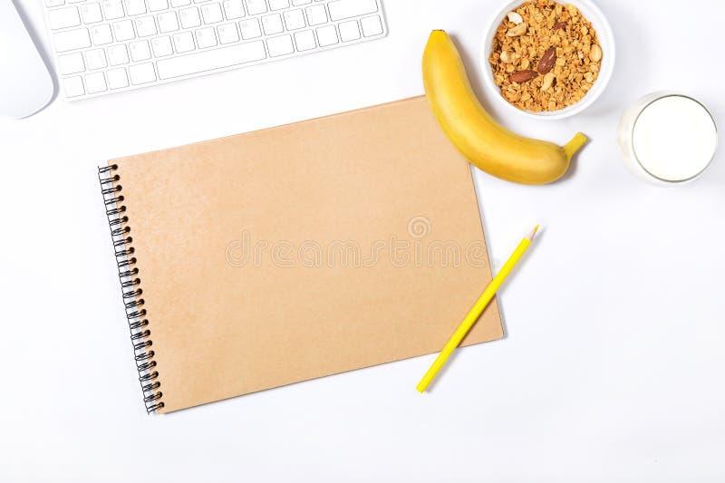 Άσπρο πληκτρολόγιο, ποντίκι, scetchbook  κίτρινα μολύβια, πιάτο με το granola, μπανάνα και ποτήρι του γάλακτος στο άσπρο υπόβαθρο στοκ εικόνες