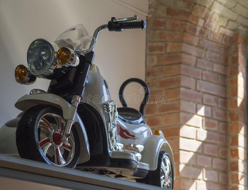 Άσπρο ποδήλατο μοτοσικλετών παιχνιδιών παιδιών με τούβλινος και άσπρος στοκ εικόνες με δικαίωμα ελεύθερης χρήσης