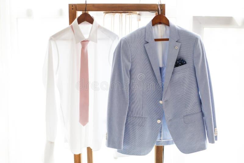 Άσπρο πουκάμισο και γκρίζο κοστούμι της ένωσης νεόνυμφων στην κρεμάστρα στοκ εικόνες