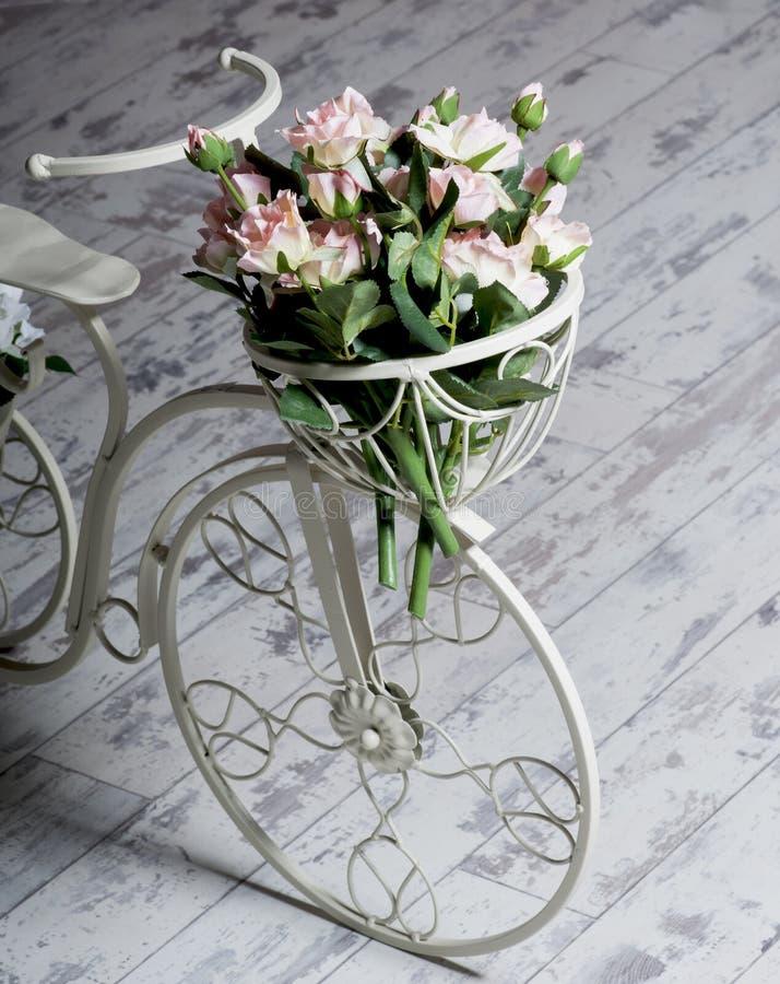 Άσπρο ποδήλατο κήπων με ένα καλάθι των τριαντάφυλλων λουλουδιών στοκ εικόνες