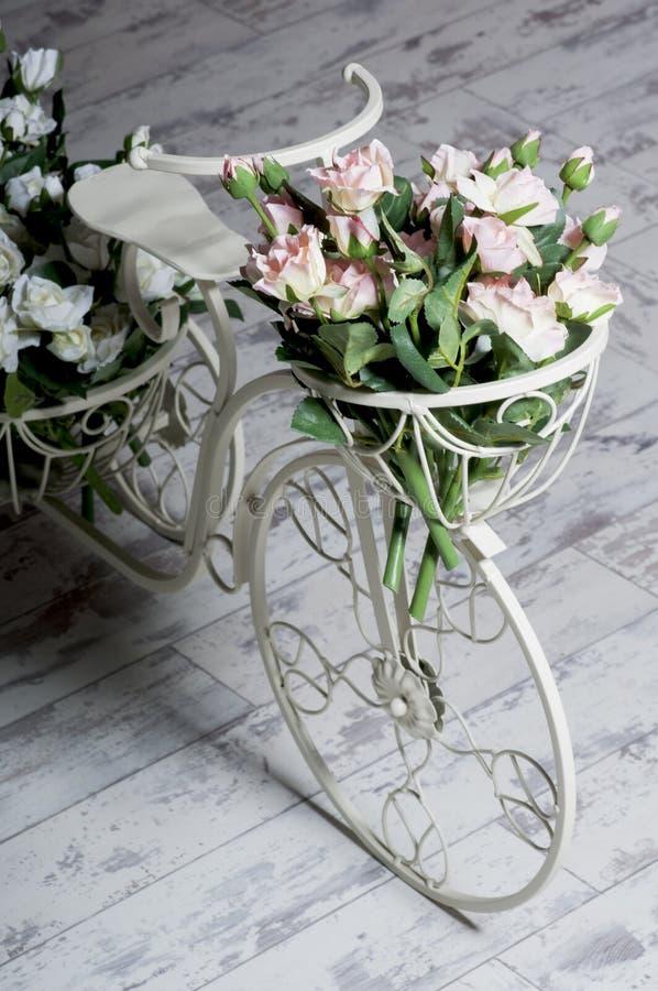 Άσπρο ποδήλατο κήπων με ένα καλάθι των τριαντάφυλλων λουλουδιών στοκ εικόνα