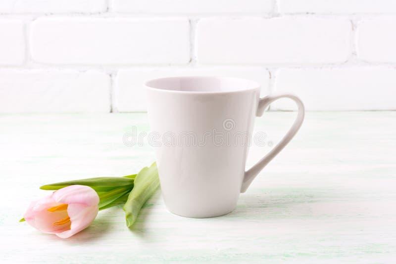 Άσπρο πρότυπο κουπών καφέ latte με τη ρόδινη τουλίπα στοκ εικόνα