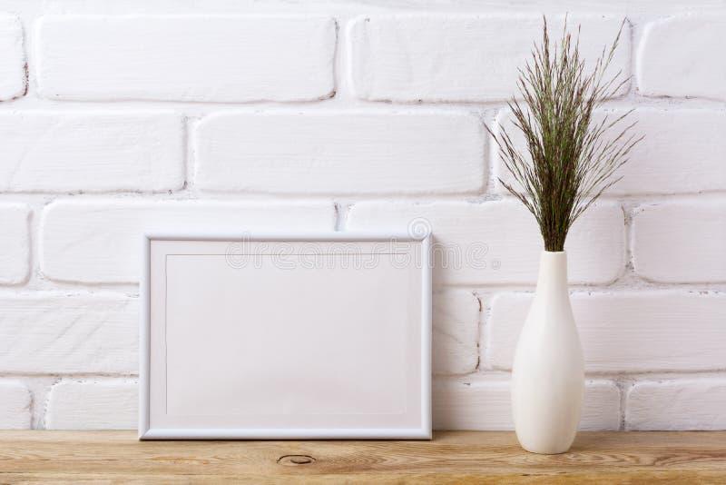 Άσπρο πρότυπο πλαισίων τοπίων με τη σκοτεινή χλόη στο κομψό βάζο στοκ εικόνα με δικαίωμα ελεύθερης χρήσης